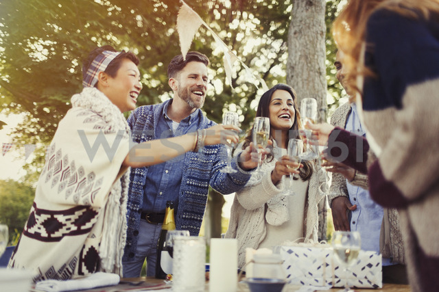Friends toasting champagne glasses at patio table - CAIF16011