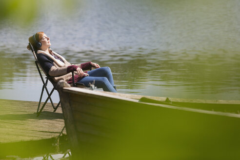 Serene woman relaxing listening to music with headphones at sunny lakeside dock - CAIF16020