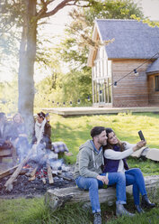 Couple taking selfie with camera phone at campfire outside cabin - CAIF16047