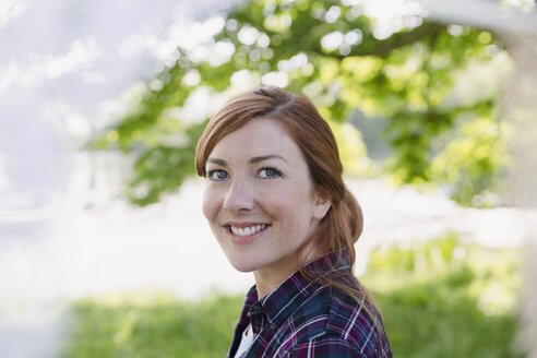 Portrait smiling woman with red hair outdoors - CAIF16050