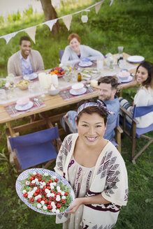 Portrait smiling woman serving Caprese salad to friends at garden party table - CAIF16059