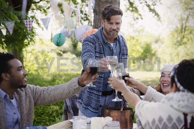 Friends toasting wine glasses at garden party table - CAIF16065