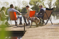 Friends and dog at sunny lakeside dock - CAIF16080