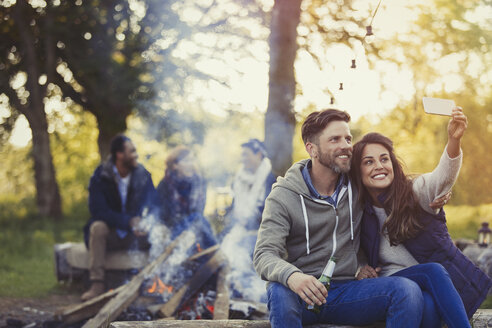 Smiling couple taking selfie with camera phone near campfire - CAIF16089