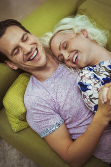 Affectionate laughing couple laying on sofa with eyes closed - CAIF16092