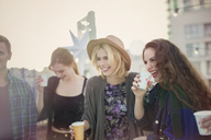 Smiling young women drinking and laughing at rooftop party - CAIF16119