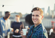 Portrait smiling young man drinking at rooftop party - CAIF16131