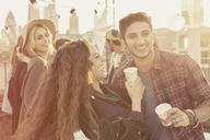 Young adult friends drinking and laughing at rooftop party - CAIF16158