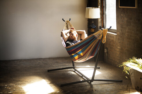 Man looking away while relaxing in hammock tied on stand at home - CAVF07894