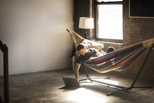 Man using laptop computer while lying in hammock tied on stand at home - CAVF07897
