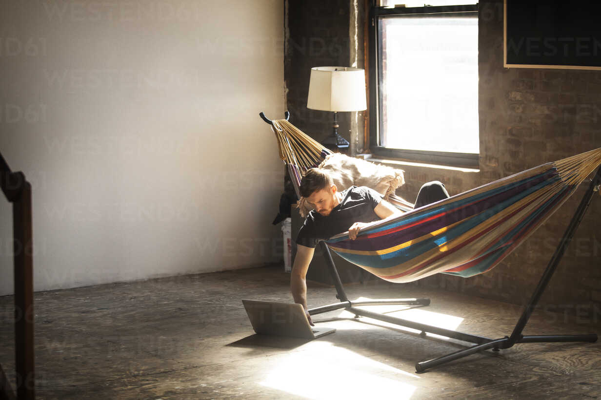 Man using laptop computer while lying in hammock tied on stand at home - CAVF07897 - Cavan Images/Westend61