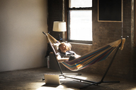 Man relaxing in hammock tied on stand - CAVF07903