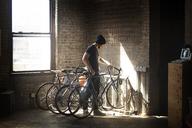 Man keeping bicycle in rack - CAVF07909
