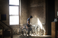 Man standing by bicycles at home - CAVF07912