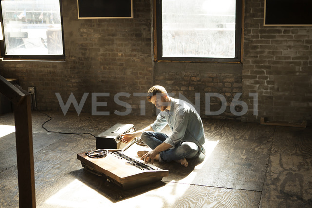 Man playing piano while tuning audio equipment at home - CAVF07927 - Cavan Images/Westend61