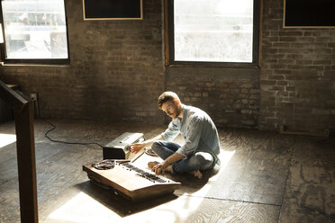 Man playing piano while tuning audio equipment at home - CAVF07927