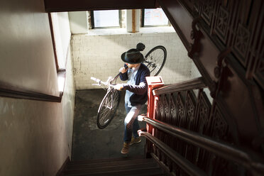 High angle view of man carrying bicycle while climbing stairs at home - CAVF07939