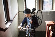 Man looking away while carrying bicycle on shoulder at home - CAVF07942