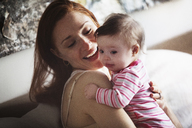 Happy mother embracing daughter while sitting on sofa at home - CAVF07978