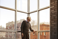 Man looking away while standing by window at home - CAVF08059