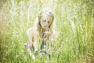 Woman sitting in grassy field - CAVF08080