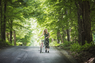 Woman with bicycle walking on road amidst trees - CAVF08086