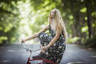 Woman looking up while sitting on bicycle - CAVF08089