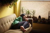 Woman lying on sofa at home - CAVF08101