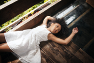 High angle view of girl lying on floor in tree house - CAVF08113