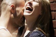 Cheerful couple against brick wall - CAVF08134