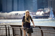 Cheerful woman cycling by railing against East River - CAVF08143