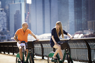 Cheerful couple cycling by railing against buildings - CAVF08146