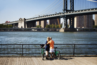 Rear view of couple with bicycles standing against Manhattan Bridge - CAVF08149