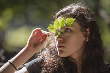 Teenage girl looking away while holding plant stem - CAVF08182