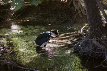 Side view of teenage girl holding water while crouching in stream - CAVF08185