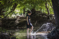 Teenage girl splashing water while standing in stream at forest - CAVF08188