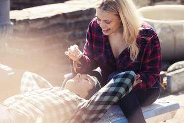 Smiling woman holding dry leaf while man lying on bench - CAVF08260