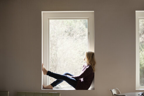 Side view of thoughtful woman sitting on window sill at home - CAVF08266