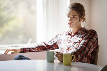 Thoughtful man holding coffee mug while sitting by window at home - CAVF08269