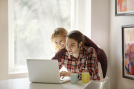 Happy couple using laptop together at home - CAVF08272