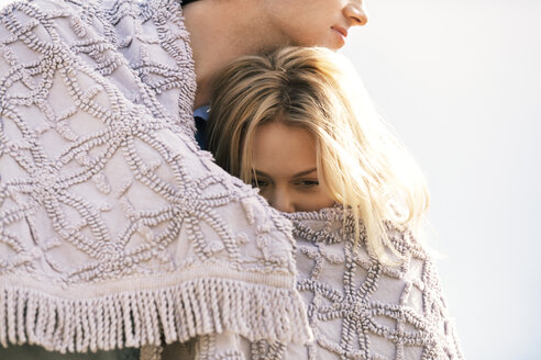 Romantic couple wrapped in blanket outdoors - CAVF08275