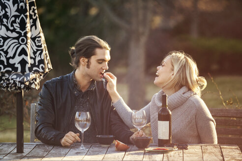 Cheerful woman feeding man at picnic table in park - CAVF08278