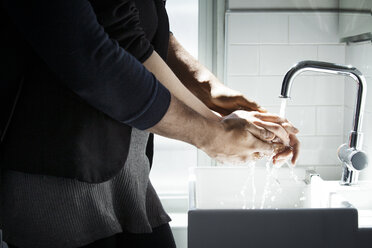 Midsection of loving couple washing hands in bathroom - CAVF08287