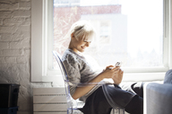 Side view of happy woman using smart phone at home - CAVF08293