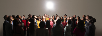 Diverse crowd looking up at bright light - CAIF16212