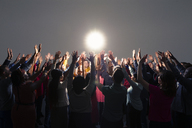Diverse crowd with arms raised around bright light - CAIF16218