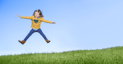 Girl jumping for joy on grassy hill - CAIF16239