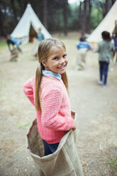 Girl smiling in sack at campsite - CAIF16251