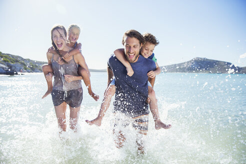 Family running in water on beach - CAIF16290