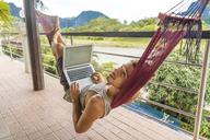 Laos, Vang Vieng, young man lying in hammock using laptop - AFVF00297